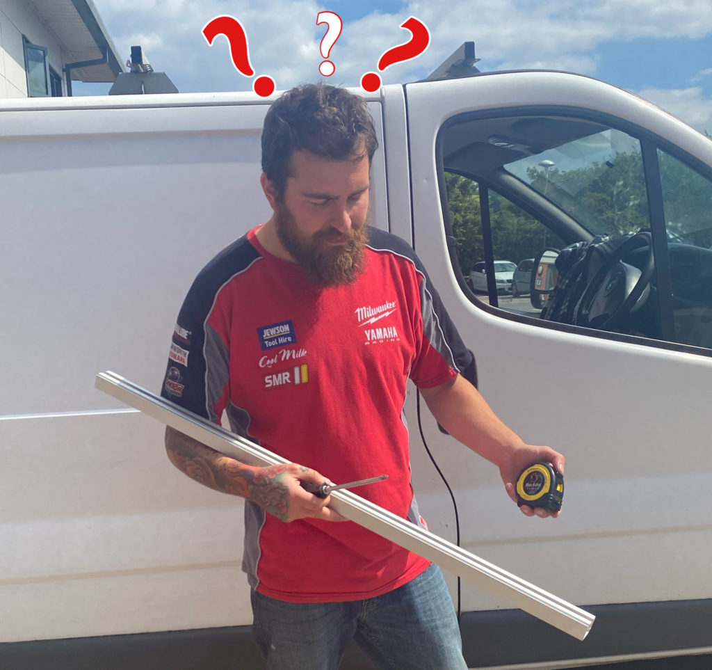 A man looking confused, holding a sliding door track and some tools.